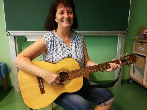 Zu sehen ist Frau Betge mit einer Gitarre. Sie leitet den Singkreis.